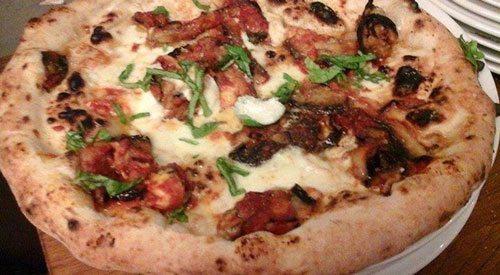 Pizza-con-parmigiana-di-melanzane,-mozzarella-affumicata,-strutto-e-basilico
