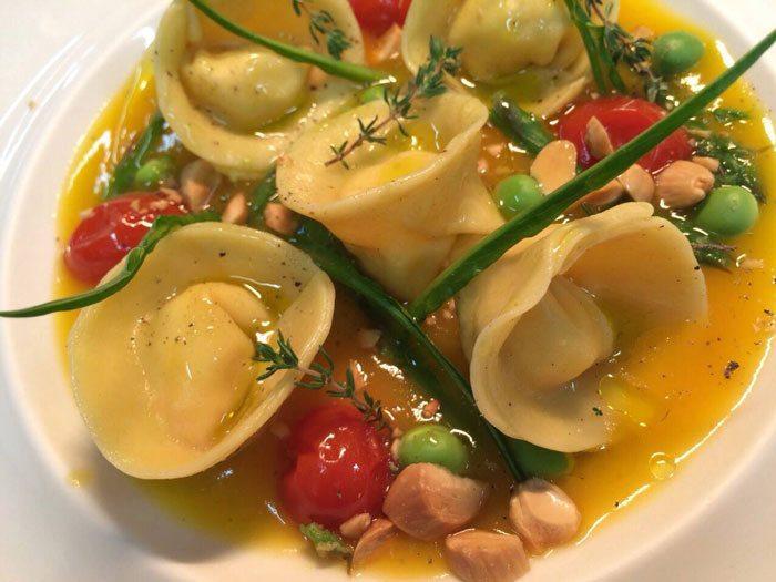 Ravioli-di-crostaceo-su-crema-di-datterini-gialli-e-mandorle-tostate