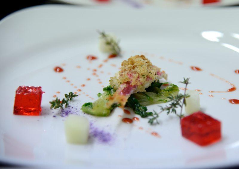 Triglia gratinata al forno su letto di scarole e riduzione di Chiaretto, con cubetti di melone e gelatina di Chiaretto, opera dello chef Michele